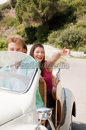 young people driving convertible car