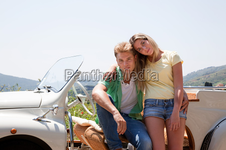 young couple by convertible car looking