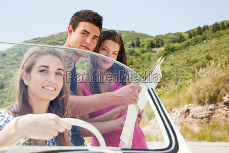 young friends with convertible car looking