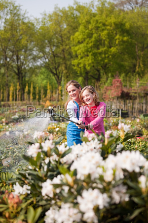 woman and girl watering plants with