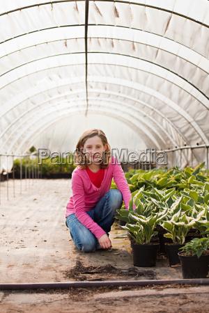 girl kneeling by plants in polytunnel