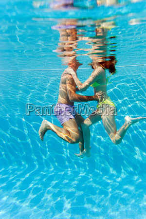young couple embracing in swimming pool