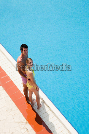 young couple standing at poolside