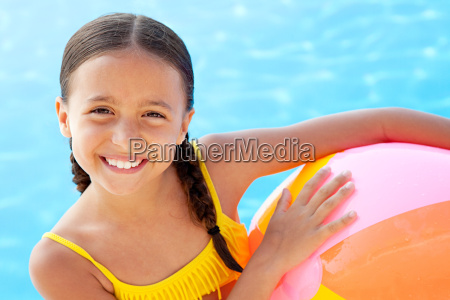 girl with beach ball by swimming