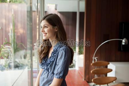 happy young woman looking through window