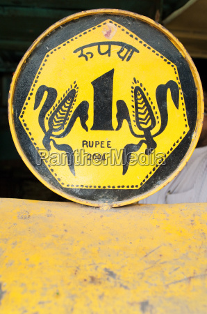 yellow tin rupee sign for public