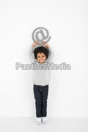 boy holding an at symbol