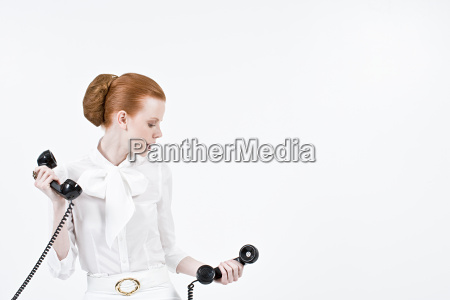 a businesswoman holding telephone receivers