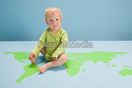 baby girl sitting on world map