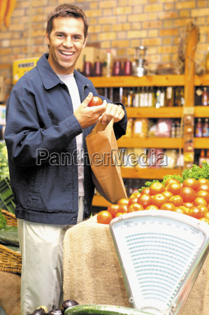 man holding tomato and paper bag