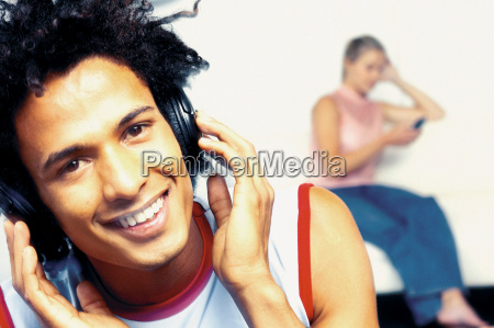 man listening to headphones with woman