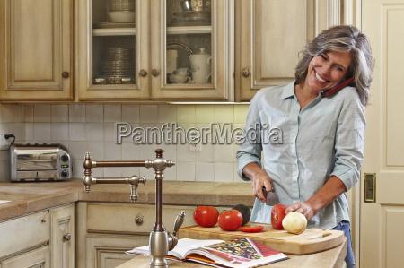 mature woman using mobile and preparing