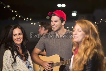 young adult friends enjoying guitar music