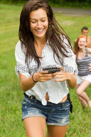 teenage girl looking at mobile phone