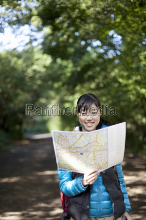 young female hiker looking at map