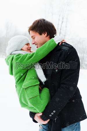 father holding daughter in snow