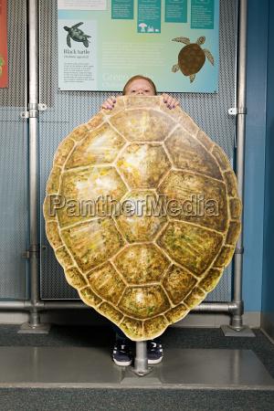 girl standing behind loggerhead sea turtle