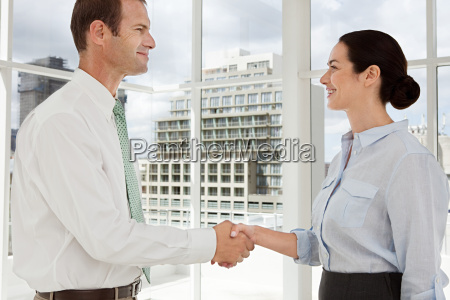businessman and businesswoman shaking hands in