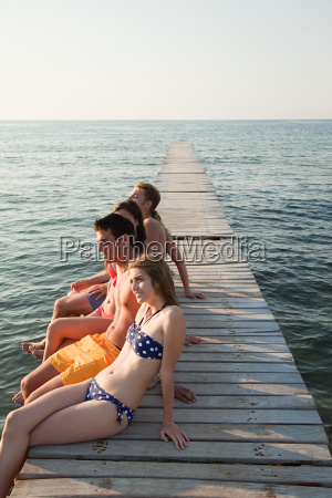 young friends sitting on jetty