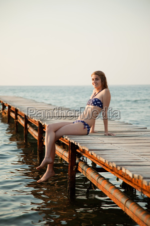 young woman sitting on jetty portrait