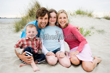 young family sitting on beach portrait