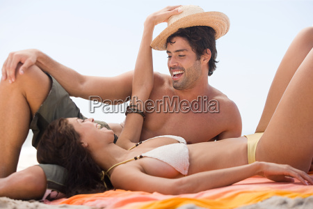 young couple playing on a beach
