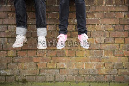 legs of teenagers on wall