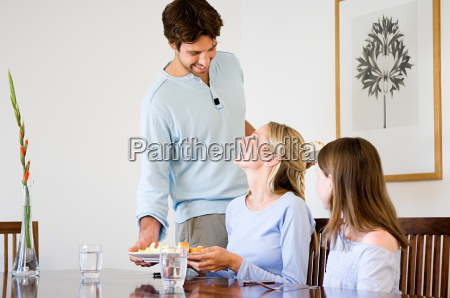 young man serving food to family