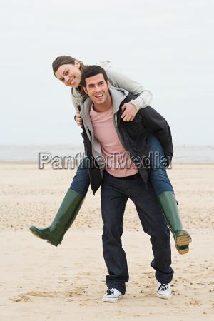 man giving woman a piggyback on
