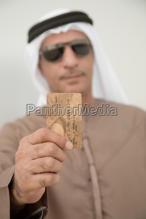 middle eastern man holding credit card