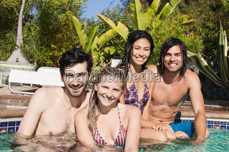 young friends in swimming pool on