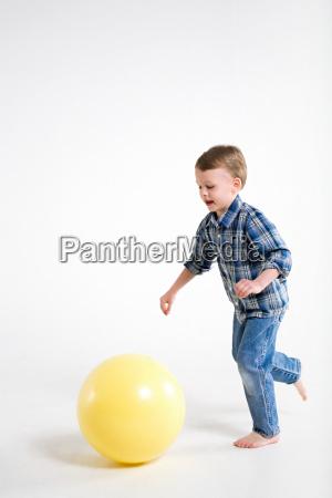 a boy running after a ball
