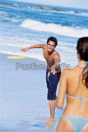 man and woman playing frisbee on