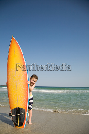 boy holding surfboard on its end