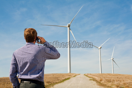 man on mobile phone watching wind