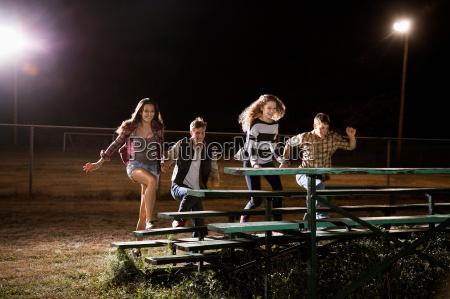 four friends walking over bleachers at