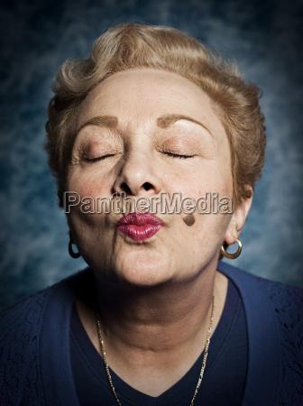 senior woman blowing kiss eyes closed
