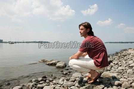 mid adult man crouching on beach