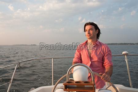 mid adult man steering yacht