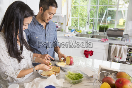 mid adult couple preparing sandwich at