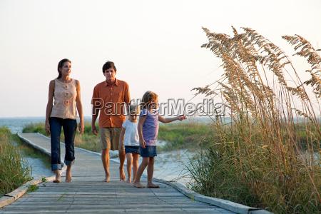 family walking on beach walkway