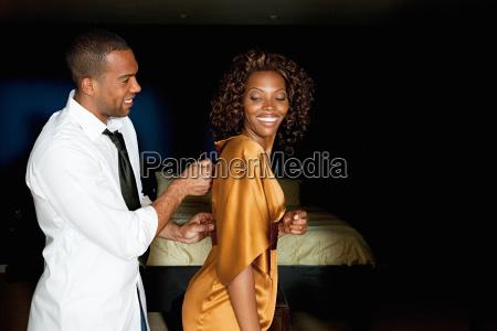 man zipping up girlfriends dress
