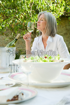 mature woman holding glass of white