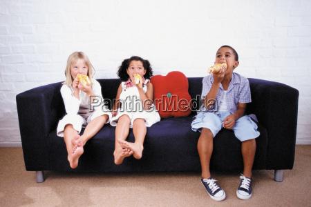 boy and girls eating on sofa
