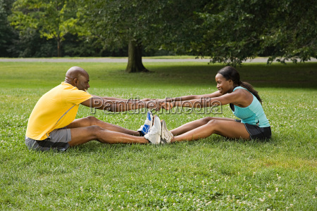 man and woman stretching in park