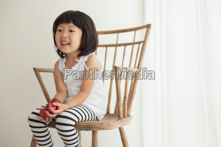girl sitting on wooden chair portrait
