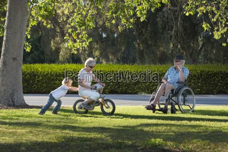 three year old boy pushing grandmother