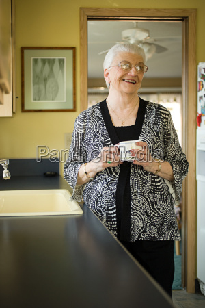 smiling senior woman holding a cup