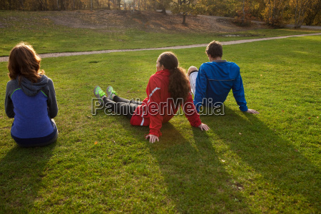 three young friends sitting on grass