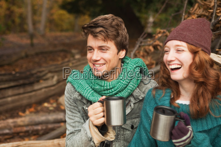 young couple in forest holding flasks